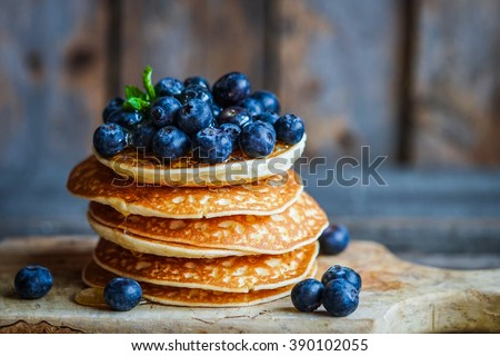 Blueberry pancakes on rustic wooden background - stock photo