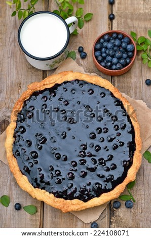 Blueberry pie, cup of milk and fresh berries on rustic wooden table, top view - stock photo