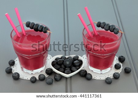 Blueberry smoothie health juice drink with fresh fruit on wooden grey background. - stock photo