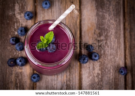 Blueberry smoothie in a glass jar with a straw and sprig of mint, over vintage wood table with fresh berries. - stock photo