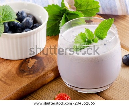 Blueberry smoothie in a glass with fresh berries. Selective focus - stock photo