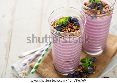 Blueberry smoothie with granola and fresh berries intall glasses - stock photo