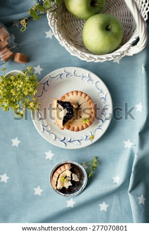 Blueberry tart set with apples and sugar by a window. Natural light photo. Overview. - stock photo