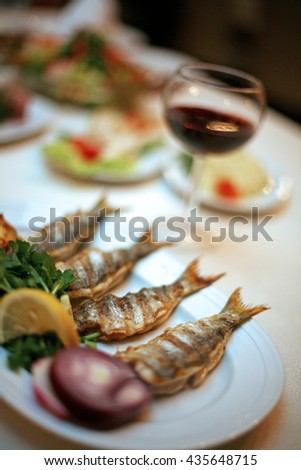 Bluefish (Turkish: Cinekop-Lufer) with red wine on the restaurant table. - stock photo