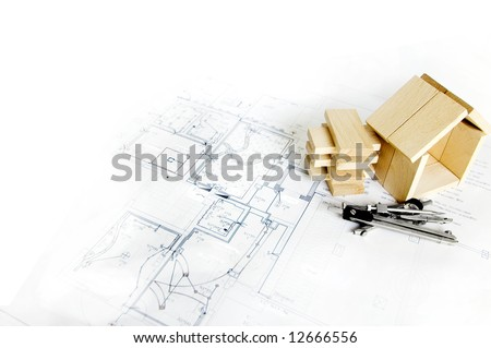 blueprint and wooden model of house - stock photo