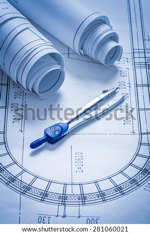 Blueprint rolls and pair of compasses construction concept
