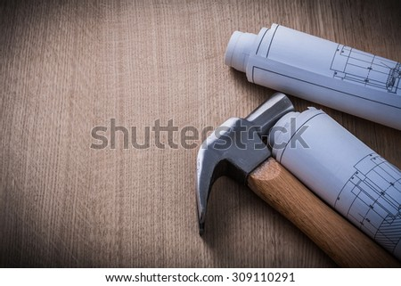 Blueprint rolls claw hammer on wooden background construction concept.