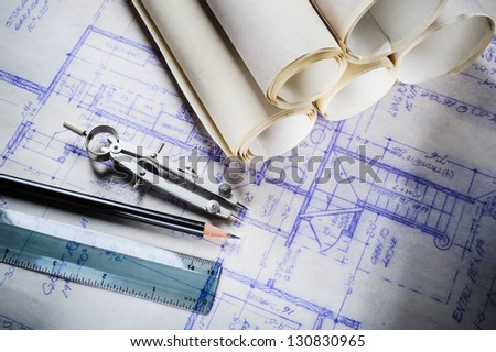 blueprints and drafting tools on a desk - stock photo