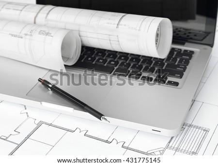 Blueprints and laptop - stock photo