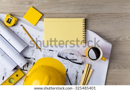 Blueprints, Hardhat, Glasses, Stickers, Construction level, Pen and Coffee in architecture office - stock photo