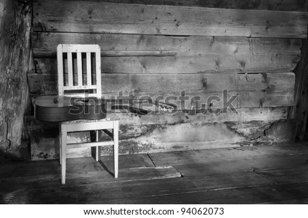blues guitar on an old wooden chair at the wall as background black and white