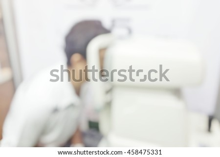 Blur abstract background a man with cabinet ophthalmic eye examination. Blurry view of male patient in ophthalmology clinic during the study of computer vision defects. - stock photo