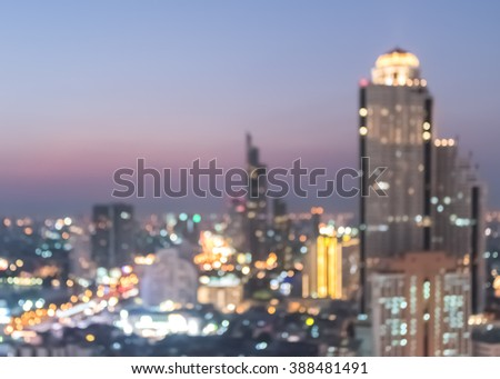 Blur abstract background aerial view of Bangkok cbd downtown city night lights colorful bokeh in cool pink blue golden hour tone: Central business district on electric train line road over river - stock photo