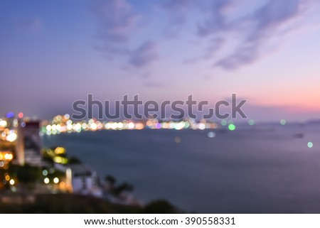 Blur abstract background cityscape bokeh nightlife illuminated night light on ocean bay beachfront waterscape of tourist city: Blurry rooftop aerial view of Pattaya beach seaside twilight sky - stock photo