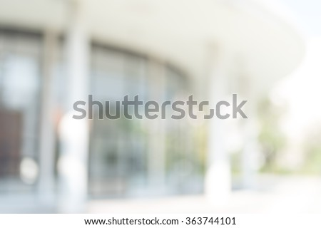 Blur abstract background exterior view looking out toward to empty office lobby and entrance doors/ glass curtain wall with frame: Blurry perspective of reception hall to public building entrance - stock photo