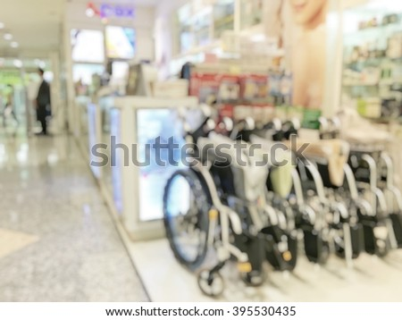 Blur abstract background inside pharmacy store with shelves of pharmaceutical, cosmetic products, medical supplies stretcher, wheelchair : Blurry view indoor space drug store/ shop interior space  - stock photo