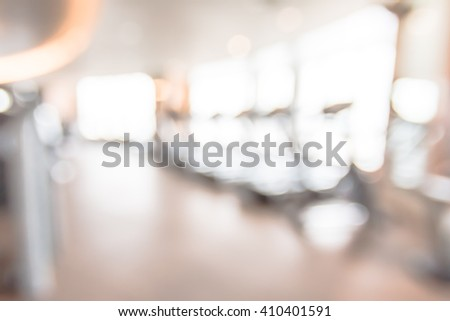Blur abstract background modern fitness center with health exercise equipment : Blurry perspective view of gym facility service room: Empty gymnasium indoor space for diet, bodybuilding and training  - stock photo