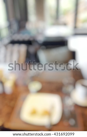 Blur abstract background of beautiful urban restaurant interior with wooden yellow cozy chairs and tables with bokeh blurred. Blurry view of food on plate on table in hotel restaurant. - stock photo