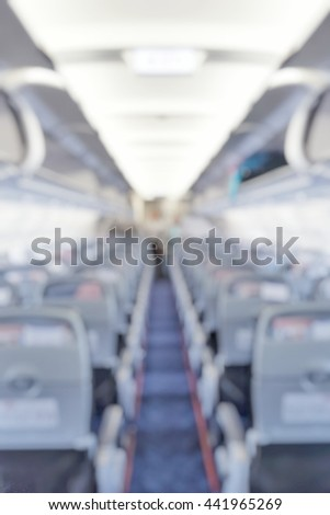 Blur abstract background of empty seats for passengers in airplane view from rear of plane. Blurry view of aisle in aircraft with cabin crew at the end.  - stock photo