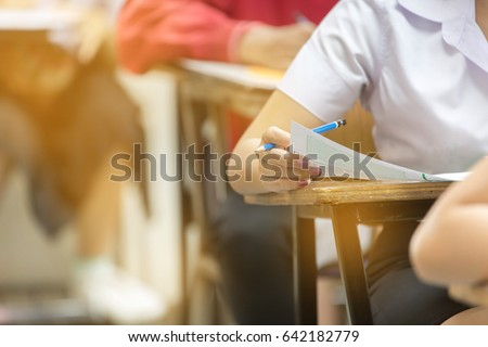 Blur abstract background of examination room with undergraduate students inside. student sitting on row chair doing final exam in classroom.