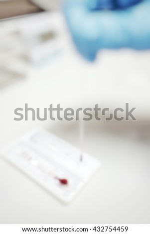 Blur abstract background of scientist technician hand pipetting blood scientific test in the microbiology laboratory. Blurry view blood in lab testing with small glass pipette. Defocus  experiment lab - stock photo