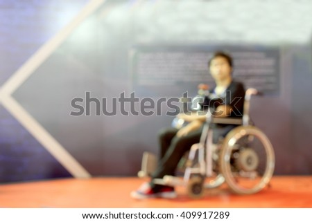 Blur abstract background perspective view of a man on wheelchair seat on the orange floor. - stock photo