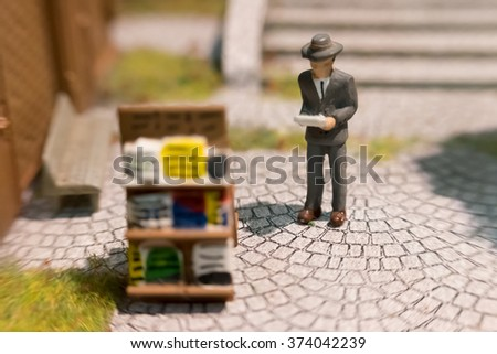 blur and soft focus tiny little model figurine of a private investor standing reading the financials and updated market reports in the paper - stock photo