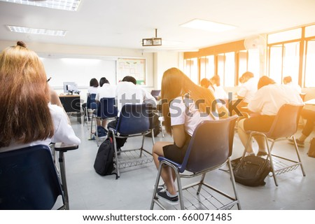 Blur Back View Abstract Background Of Examination Room With Undergraduate Students Inside University Student In
