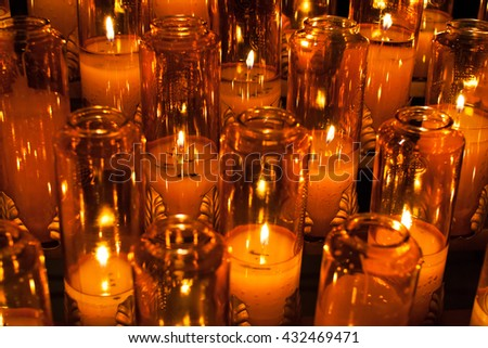 blur background of burning candles in orange transparent chandeliers in a church setting - stock photo