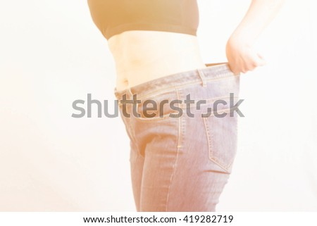 blur background portrait of slim waist of young woman in big jeans showing successful weight loss - stock photo