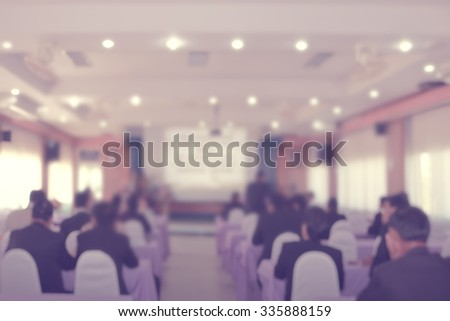 Blur Blurred business people in seminar watching new products on screen display - stock photo