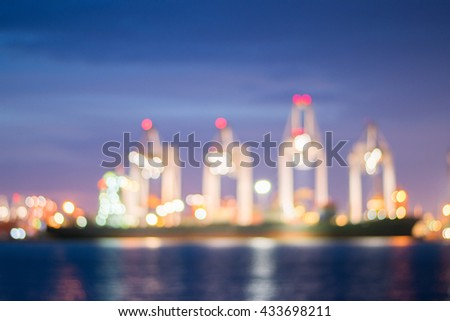 Blur bokeh of harbor with Container Cargo freight ship and crane at night. - stock photo
