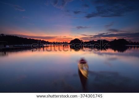 Blur canoe due to long exposure on water during sunset - stock photo