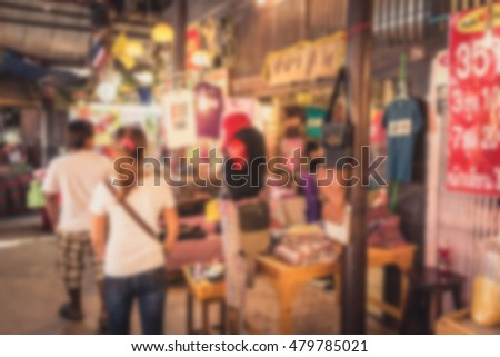 Blur effect of floating market has a many foreign visitors with varieties of Thai clothes and Thai food at Thailand