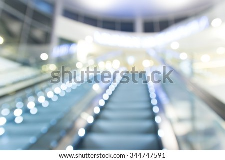 blur escalator in shopping mall with bokeh for background - stock photo