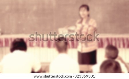 Blur female teacher showing media in hand in front of classroom listening for lecture and school project home work - stock photo