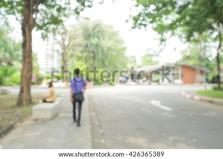 blur footpath and walkway in the park, blur a man walk on sidewalk and woman sit on bench in the park for relax, place to exercise and relax,good weather, blur big tree in the park,abstract background - stock photo