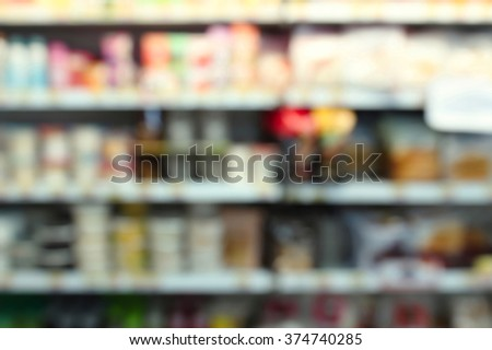 Blur image of aisle in supermarket with customers - stock photo