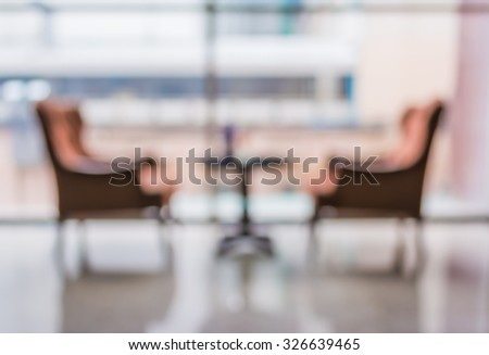 blur image of Beautiful vintage sofa next to window in lobby for background usage. - stock photo