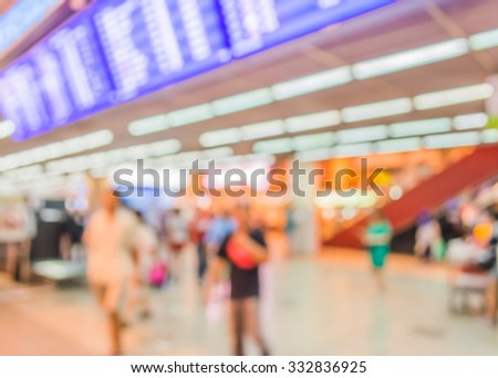 blur image of blue screen flight schedules and people in airport for background usage. - stock photo