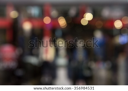 Blur image of boutique window with dressed mannequins. Boutique display window with mannequins in fashionable dresses - stock photo