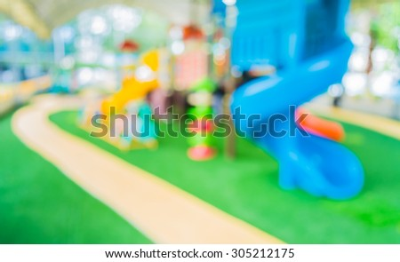 blur image of children's playground at public park for background usage.