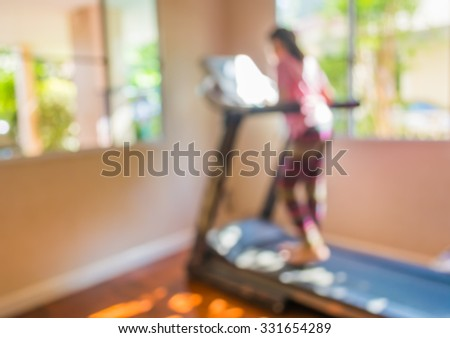 blur image of Cute girl running treadmill on day time for background usage.