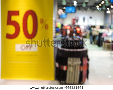 Blur image of discount signs sales store in background. - stock photo