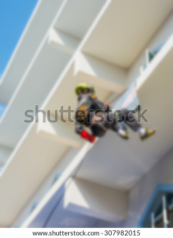 blur image of  Firefighter practice rappelling on tall building.
