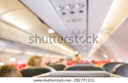 blur image of inside the airplane with people. - stock photo