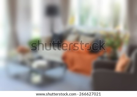blur image of modern living room design with orange sofa and black pillows - stock photo