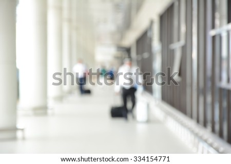 Blur image of people (travelers) walking in airport corridor, can be used for background - stock photo