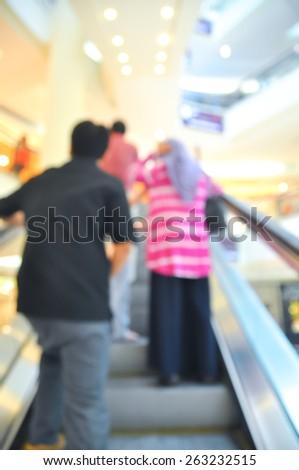 Blur image of people using escalator  - stock photo