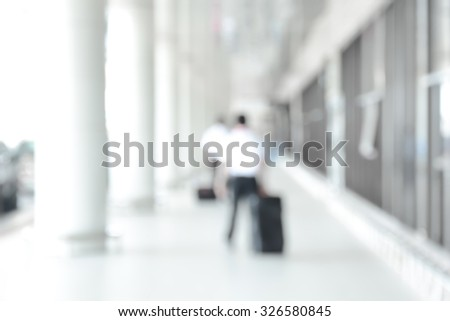Blur image of people walking in airport corridor - stock photo